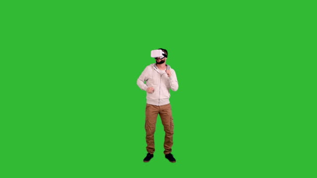 young man with glasses of virtual reality dancing on a green background video