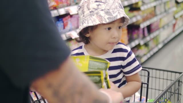 Young man with little baby boy in Grocery Store Asian father and son shopping for groceries. Thailand. snack aisle stock videos & royalty-free footage