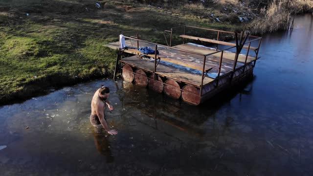 vidéos et rushes de un jeune homme aux cheveux longs et au corps fort, les bras tendus debout sur le rivage par un lac gelé - un homme entrant dans l'eau glacée - un jeune homme fort avec un corps musclé, renforce son corps debout un jour d'hiver - vue de la montagne - prendre un bain
