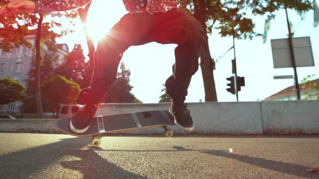 スローモーション: 長髪の若い男は、彼のスケート ボードのトリックを土地に失敗しました。 - 都市 モノクロ点の映像素材/bロール