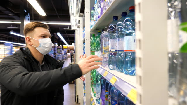 Young man with medical face mask choosing and buying bottle of water at supermarket. Guy buys drinks in store. Shopping in the grocery during coronavirus pandemic. Young man with medical face mask choosing and buying bottle of water at supermarket. Guy buys drinks in store. Shopping in the grocery during coronavirus pandemic. department store stock videos & royalty-free footage
