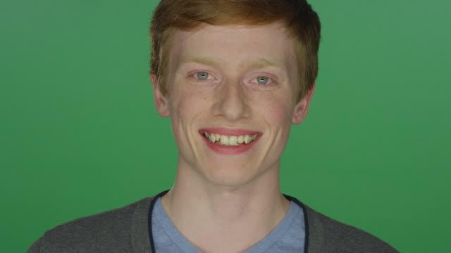ung man med rött hår och fräknar leende, på en grön skärm studio bakgrund - rött hår bildbanksvideor och videomaterial från bakom kulisserna