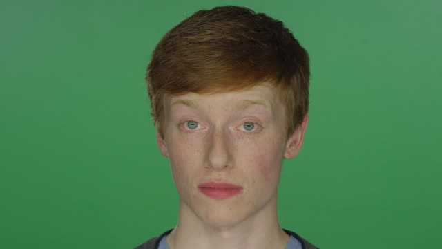 young man with red hair and freckles wiggling his ears and forehead, on a green screen studio background - rude włosy filmów i materiałów b-roll