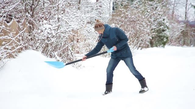 young man with shovel clears snow, then drops shovel and goes away