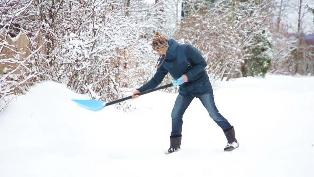 ung man med spade rensar snö, sedan droppar spade och går bort - skyffel bildbanksvideor och videomaterial från bakom kulisserna