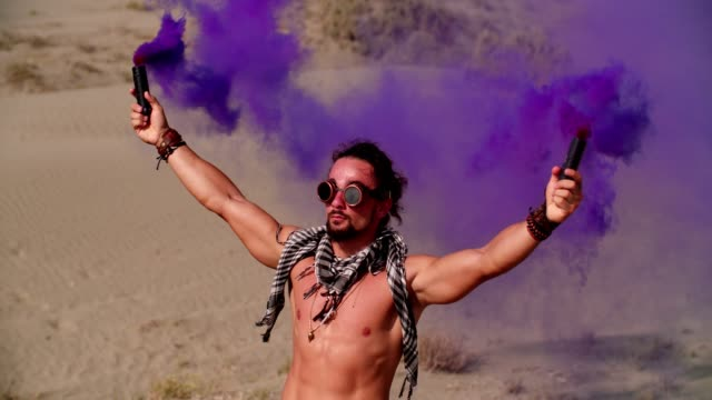 Young man with smoke bombs celebrating at desert music festival Man in steampunk style holding smoke bombs and standing in desert partying at music festival macho stock videos & royalty-free footage