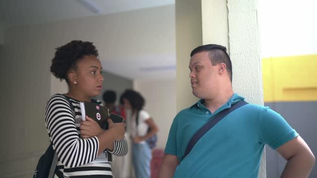 大学のキャンパスで特別なニーズを持つ若者が友人と話す - disabilitycollection点の映像素材/bロール