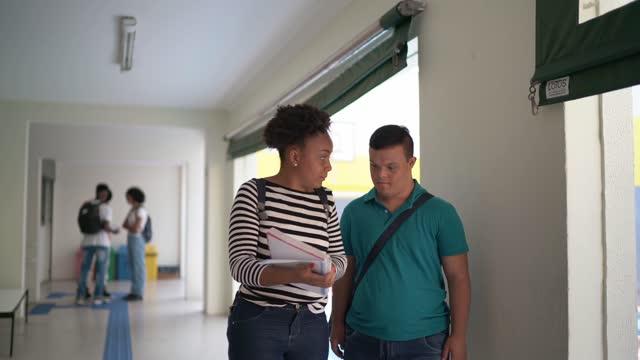 友人と話している大学のキャンパスを歩く特別なニーズを持つ若者 - disabilitycollection点の映像素材/bロール