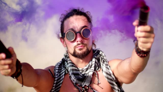 Young man with steampunk goggles and smoke bombs in desert video