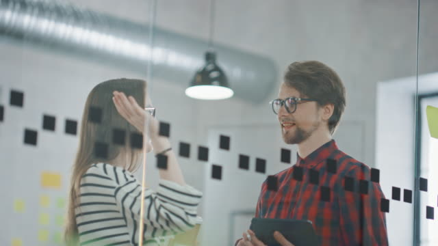 young man with tablet and woman with takeaway coffee stand before a glass wall with notes and discuss business opportunities. they work in creative agency. high five over a good project idea. - время дня стоковые видео и кадры b-roll