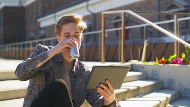 young man with tablet pc and drink on rooftop