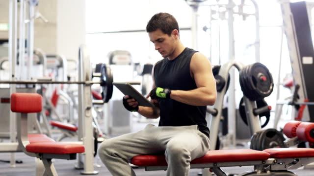 stockvideo's en b-roll-footage met jonge man met tablet pc-computer in sportschool - bankdruktoestel