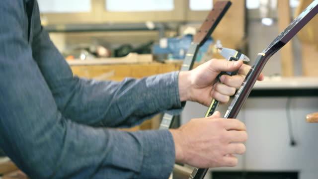 stockvideo's en b-roll-footage met young man working as craftsman in guitar workshop - alleen één mid volwassen man