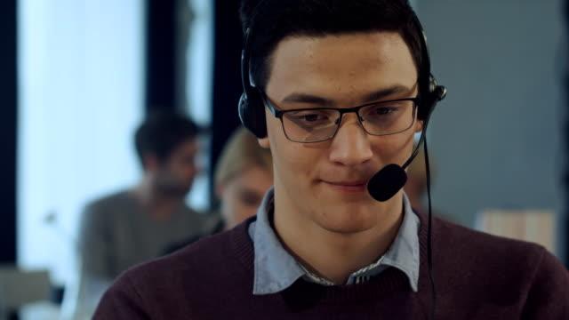 若者コール センター笑顔でコンピューターでの作業 - スパイ点の映像素材/bロール
