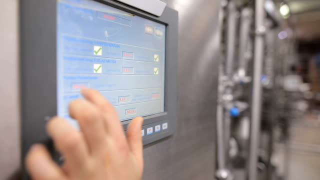 young man working at a food factory on the control station.hand on the touch screen - azionare video stock e b–roll