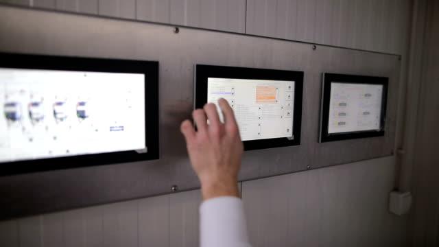 kontrol istasyonu gıda fabrikası'nda çalışan bir genç adam. dokunmatik ekranda el - gıda ve i̇çecek sanayi stok videoları ve detay görüntü çekimi