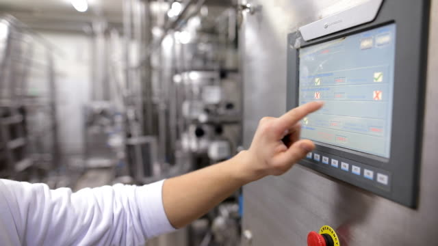 Young man working at a food factory on the control station.Hand on the touch screen