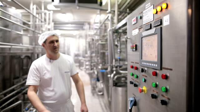 young man working at a food factory - молочный продукт стоковые видео и кадры b-roll