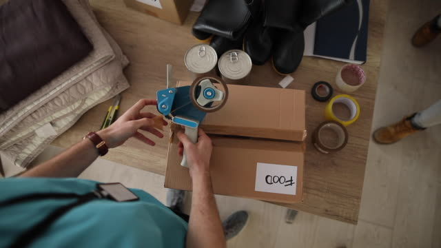Young man working at charitable foundation, packing donation box High angle view of man working at charitable foundation, taping cardboard donation box giving tuesday stock videos & royalty-free footage
