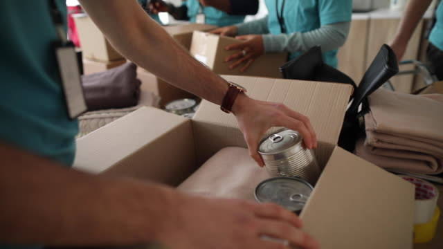 Young man working at charitable foundation, packing donation box Man working at charitable foundation, packing cardboard donation box with canned food and blanket food stock videos & royalty-free footage