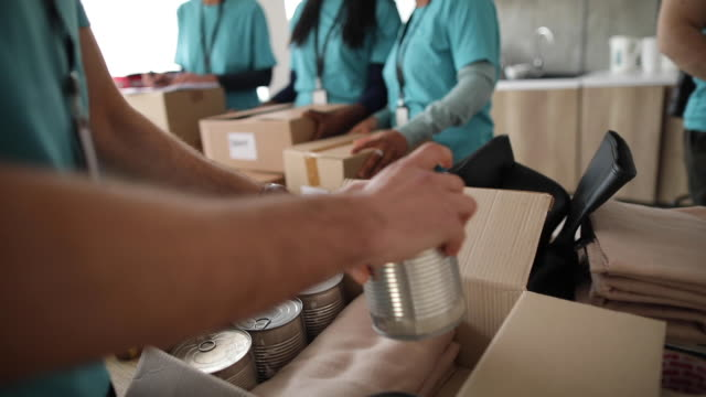 Young man working at charitable foundation, packing donation box Man working at charitable foundation, packing cardboard donation box with canned food and blanket giving tuesday stock videos & royalty-free footage