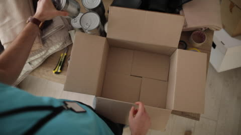 Young man working at charitable foundation, packing donation box High angle view of man working at charitable foundation, packing cardboard donation box with canned food and blanket giving tuesday stock videos & royalty-free footage