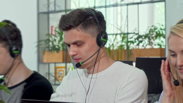 Young man working at customer support call center, wearing headset
