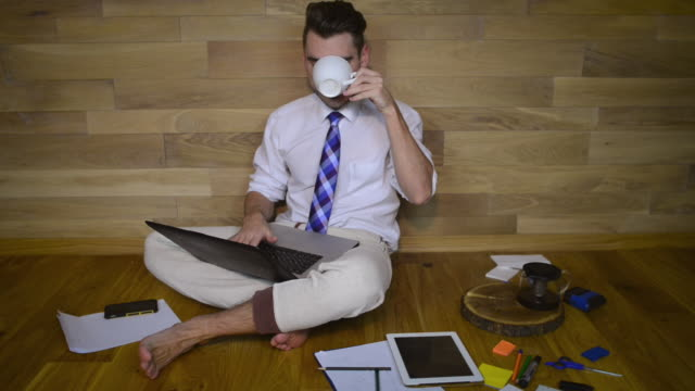 Young man working at home in pajama pants Young man working at home in pajama pants and drinking coffee or tea. Barefoot guy sitting on the floor and looking in laptop and typing. button down shirt stock videos & royalty-free footage