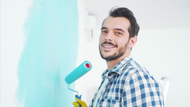 Young man working at home. Portrait of a young man painting interior walls in his new apartment. He is looking at camera with joy. house painter stock videos & royalty-free footage