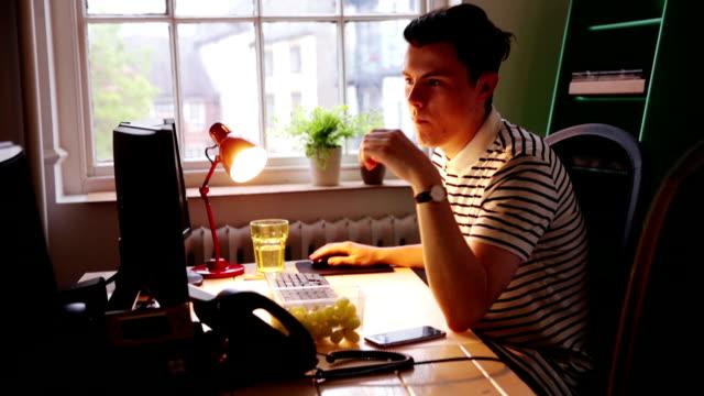vidéos et rushes de jeune homme travaillant au bureau - 18 19 ans