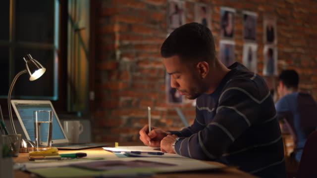 vídeos de stock, filmes e b-roll de ds jovem homem trabalhando no escritório de início à noite - nova empresa