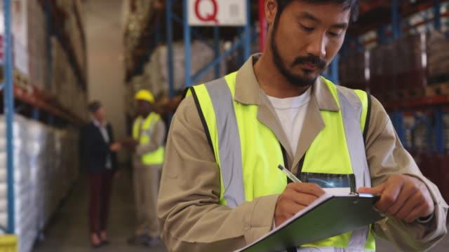vidéos et rushes de jeune homme travaillant dans un entrepôt 4k - bloc note