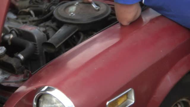 giovane uomo lavorando sul motore auto - solo un uomo giovane video stock e b–roll