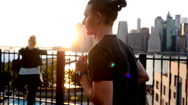 Young man working out against the New York City waterfront sunset video
