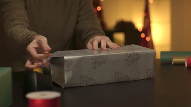 Young man wrapping up Christmas presents