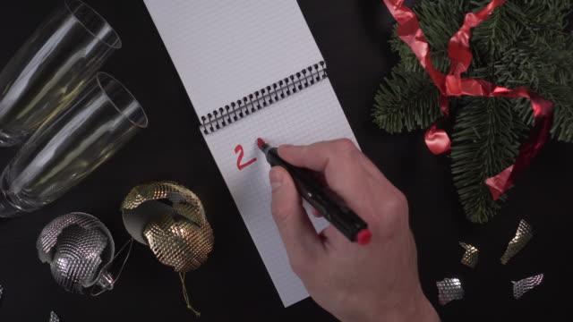 vidéos et rushes de un jeune homme écrit dans un cahier les mots 2020 goals sur une table en bois entourée d'attributs de la célébration de noel terminée. décorations cassées de noel - fête de naissance