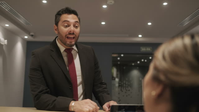 genç yöneticisi iş müşteriyle corporation resepsiyonda - hotel reception stok videoları ve detay görüntü çekimi