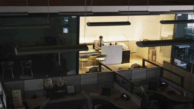 vídeos y material grabado en eventos de stock de joven director trabajando solo en una oficina vacía, elevado ver - cube