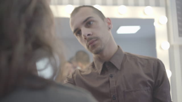 ung man, make-up artist, tillämpa rouge på unga kvinnans kind - makeup artist bildbanksvideor och videomaterial från bakom kulisserna