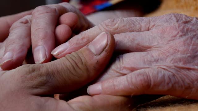 Un jeune homme de mains réconfortant une paire âgée de mains de grand-mère en gros plan, provient du soleil derrière les nuages et souligne leur - Vidéo