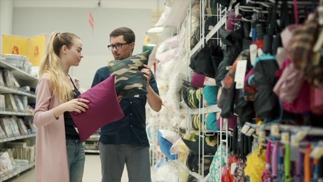 vídeos de stock, filmes e b-roll de jovem casado casal está disputando em uma loja, escolha de almofadas decorativas - decoração
