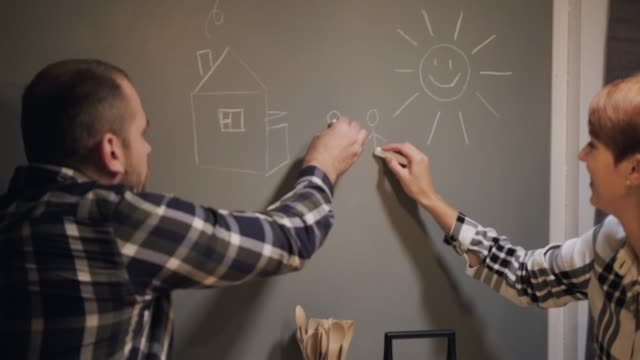 Young married couple in casual clothes, man and woman, sitting at home in the kitchen at the table. Draw their dreams with chalk on the wall.
