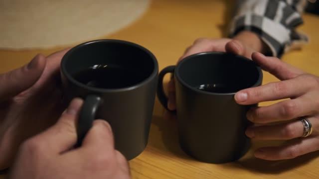 カジュアルな服装の若い夫婦、男女、テーブルの台所で自宅に座っている。魂のコミュニケーションと家庭の快適さ。 - マグカップ点の映像素材/bロール