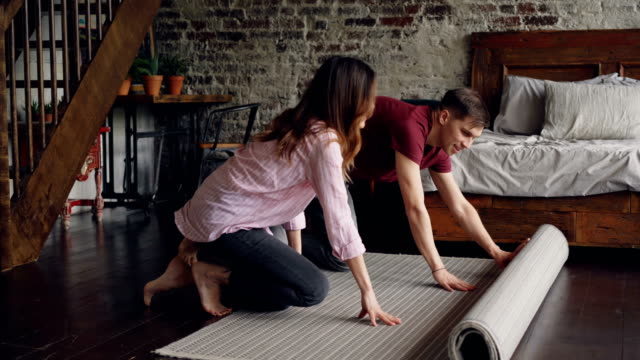 young married couple is rolling out beautiful new carpet in bedroom at home then enjoying it. house interior, married life and happy people concept. - bedroom video stock e b–roll