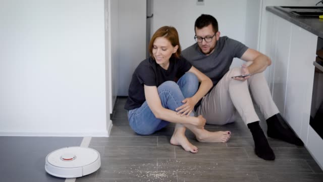 a young married couple is testing a new robot vacuum cleaner. smart home devices - gulf coast states stock videos & royalty-free footage