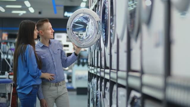 giovane coppia sposata uomo e donna nel negozio di elettrodomestici scelgono di acquistare una lavatrice per la casa. aprire la porta guardando nel tamburo, confrontare il design e le caratteristiche dei dispositivi - elettrodomestico attrezzatura domestica video stock e b–roll