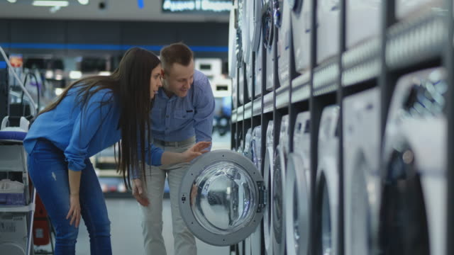 young married couple man and woman in casual clothes appliances store choose to buy washing machine for home. open the door looking into the drum, compare the design and characteristics of the devices - przemysł elektroniczny filmów i materiałów b-roll