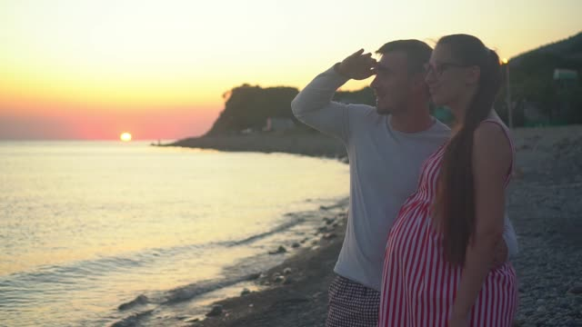 A young married couple stands on a background of sea sunset. A man and a pregnant woman are smiling.