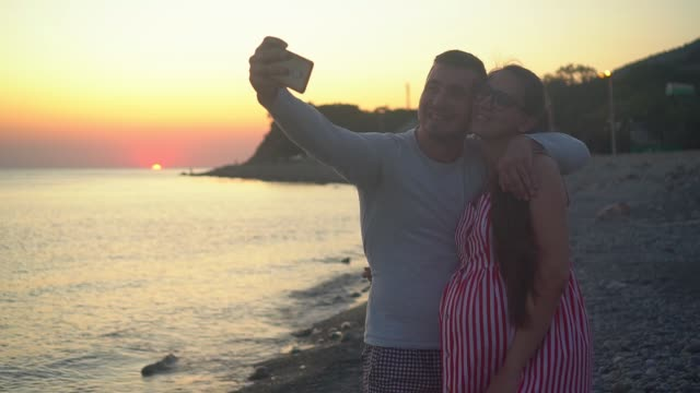 A young married couple stands on a background of sea sunset. A man and a pregnant woman are taking a selfie.