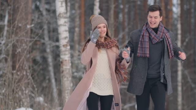 vídeos de stock, filmes e b-roll de o par casado novo anda através da floresta do inverno. um homem e uma mulher olham-se rindo e sorrindo no movimento lento - moda de inverno